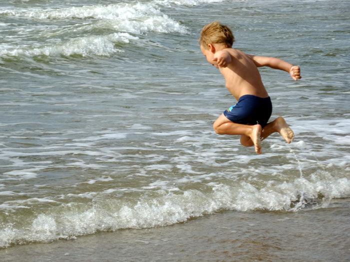 Ein kleiner Junge springt in die Wellen.