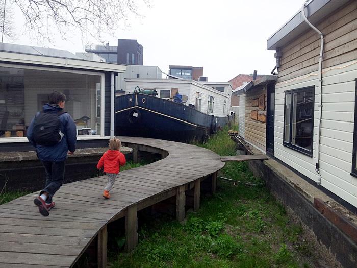 Spaziergänger bei einer Siedlung aus trockengelegten Wohnbooten.